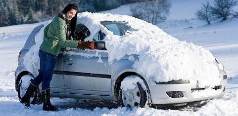 девушка чистит автомобиль от снега